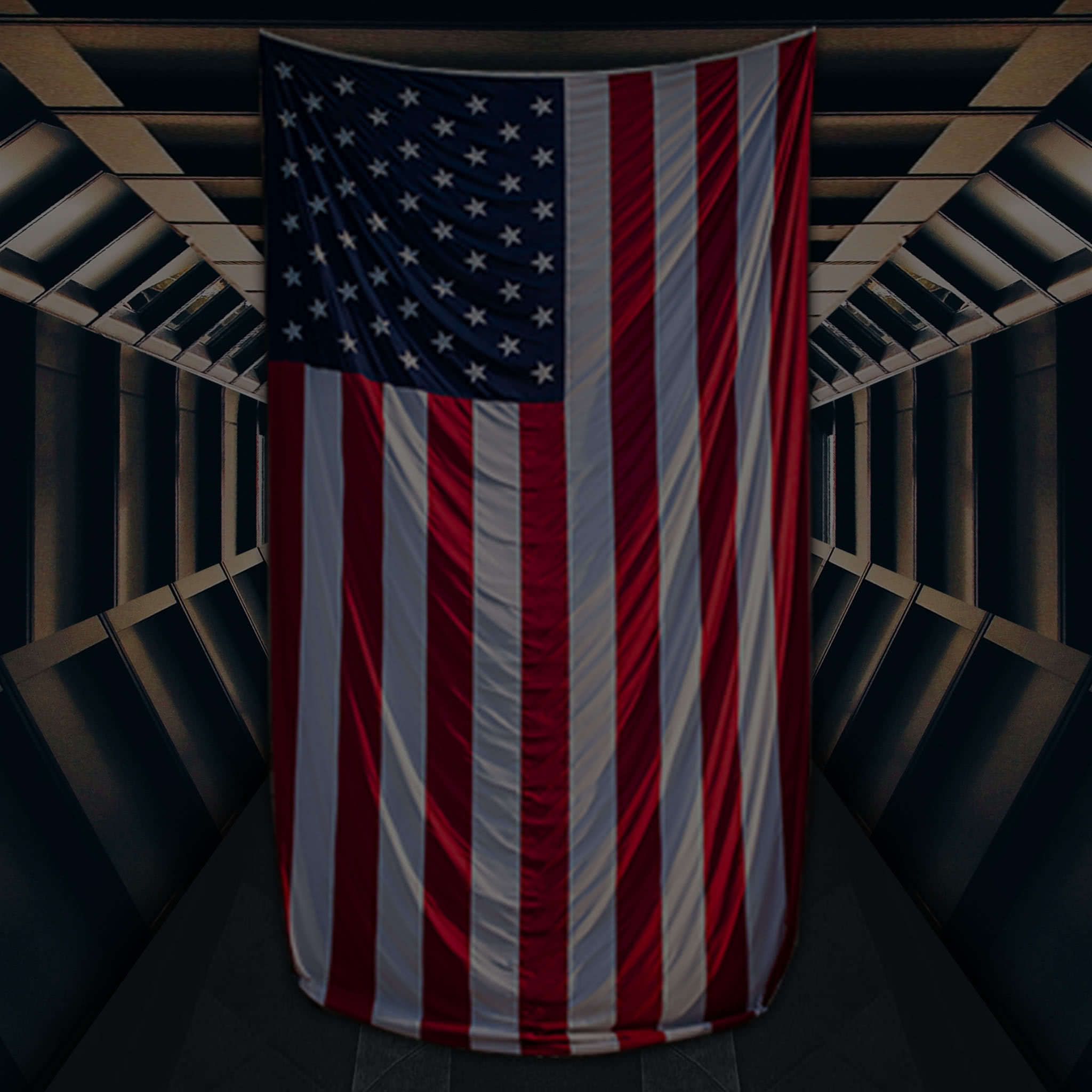 American flag hanging from the ceiling in front of a darkly lit metal corridor.